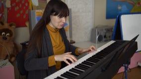 Uma jovem mulher joga um sintetizador eletrônico, suas mãos toca nas chaves filme