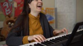 Uma jovem mulher joga um sintetizador eletrônico, suas mãos toca nas chaves vídeos de arquivo