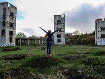 Uma jovem mulher levantou suas mãos para o céu na frente de três construções desmoronadas - vista da parte traseira Foto de Stock