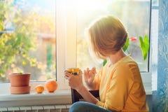 Uma jovem mulher mantém uma caneca sentar-se perto da janela no por do sol em raios brilhantes imagem de stock