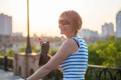 Uma jovem mulher monta uma bicicleta e bebe-a de uma garrafa dos esportes Imagens de Stock Royalty Free