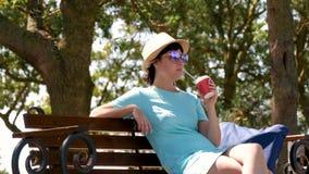 Uma jovem mulher moreno em um chapéu e em um vestido está sentando-se em um banco de parque e em um café bebendo vídeos de arquivo