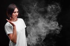 Uma jovem mulher não gosta do fumo de um cigarro ou de um cigarro eletrônico em um fundo preto Conceito da saúde foto de stock royalty free