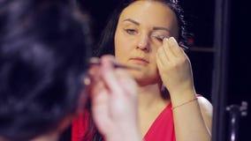 Uma jovem mulher na frente de um espelho faz a composição em seus olhos video estoque