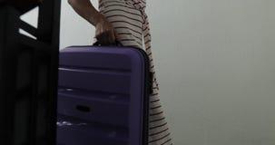 Uma jovem mulher nas sapatilhas brancas leva uma mala de viagem roxa acima das escadas video estoque