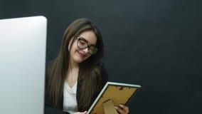 Uma jovem mulher no escritório olha a foto video estoque