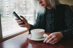 Uma jovem mulher no preto usa o telefone em um café e em um café da bebida com marshmallows Fotografia de Stock Royalty Free