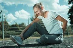Uma jovem mulher no sportswear est? sentando-se no campo de esportes e olha dolorosa imagens de stock