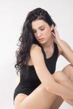 Uma jovem mulher, olhando abaixo, sentando-se foto de stock royalty free