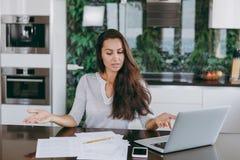 Uma jovem mulher passa o tempo em casa, na cozinha e no roo fotos de stock royalty free