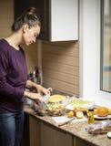 Uma jovem mulher prepara uma salada imagens de stock