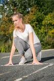Uma jovem mulher que ajoelha-se na linha de partida à corrida imagens de stock
