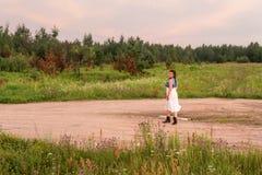 Uma jovem mulher que anda ao longo da estrada no por do sol na noite imagem de stock