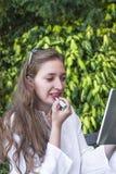 Uma jovem mulher que aplica um lipstic Imagem de Stock Royalty Free