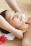 Uma jovem mulher que aprecia a massagem em termas Foto de Stock