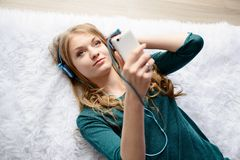Uma jovem mulher que escuta a música de seu smartphone Imagem de Stock Royalty Free