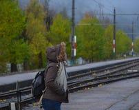 Uma jovem mulher que espera no estação de caminhos de ferro imagens de stock royalty free