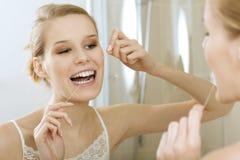 Uma jovem mulher que flossing seus dentes imagem de stock