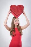 Uma jovem mulher que guarda um coração vermelho grande Fotografia de Stock Royalty Free