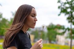 Uma jovem mulher que guarda um dente-de-leão de florescência em sua mão e que funde em uma flor imagens de stock