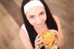 Uma jovem mulher que guarda um hamburguer em uma fita de medição Uma menina está em um fundo de madeira A vista da parte superior Imagem de Stock