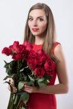 Uma jovem mulher que guarda um ramalhete grande das rosas Fotografia de Stock Royalty Free