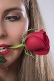 Uma jovem mulher que guarda uma rosa em sua boca Imagem de Stock