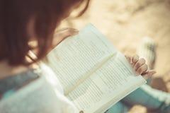 Uma jovem mulher que lê um livro Livro nas mãos da mulher Fotografia de Stock Royalty Free