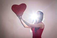 Uma jovem mulher que mantém um coração vermelho grande contra o ligth Fotos de Stock