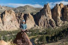 Uma jovem mulher que medita nas montanhas Imagens de Stock