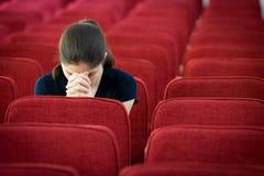 Uma jovem mulher que senta-se em rezar da cadeira Fotos de Stock Royalty Free
