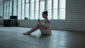 Uma jovem mulher que senta-se no assoalho toma um marcador e tira-os nas sapatas Louro bonito em um assoalho de madeira com video estoque