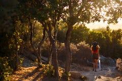 Uma jovem mulher que senta-se para trás na natureza de surpresa da ilha de Córsega, França Fundo do por do sol Vista horizontal imagem de stock royalty free