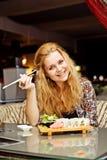 Uma jovem mulher que tem o almoço em um riso do café Fotografia de Stock
