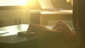 Uma jovem mulher que trabalha em uma mesa com um teclado de computador vídeos de arquivo
