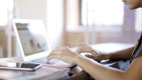 Uma jovem mulher que veste uma camisa verde que datilografa em seu portátil em um escritório Sobre o tiro do ombro Imagens de Stock Royalty Free