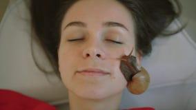 Uma jovem mulher relaxa nos termas recebe uma massagem facial com caracóis Achatina Os caracóis comem a pele inoperante do produz video estoque