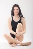 Uma jovem mulher, roupa de banho de assento, pés cruzados Imagens de Stock Royalty Free