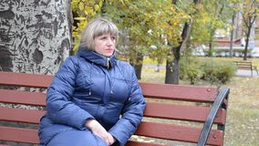 Uma jovem mulher senta-se em um banco em um parque da cidade filme