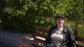Uma jovem mulher senta-se em um banco video estoque