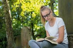 Uma jovem mulher senta-se em um parque e lê-se um livro fotografia de stock