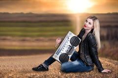 Uma jovem mulher senta-se na estrada e na escuta um gravador do vintage imagens de stock royalty free