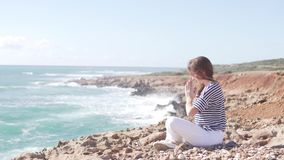 Uma jovem mulher senta-se pelo mar e faz-se ginástica video estoque