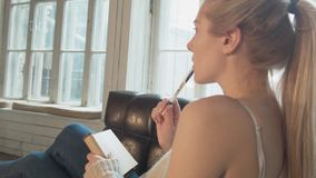 Uma jovem mulher 'sexy' escreve um nó que encontra-se em uma cadeira Um louro bonito faz anotações em um bloco de notas com uma p filme