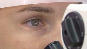 Uma jovem mulher submete-se a um exame ophthalmological, verificando a saúde dos olhos e da acuidade visual video estoque