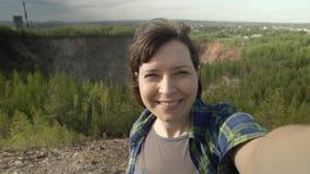 Uma jovem mulher toma um autorretrato usando um telefone nas montanhas video estoque
