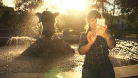 Uma jovem mulher toma um selfie em um telefone perto de uma fonte em um parque público filme