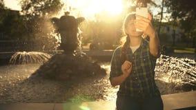 Uma jovem mulher toma um selfie em um telefone perto de uma fonte em um parque público vídeos de arquivo