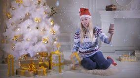 Uma jovem mulher toma um selfie sob uma árvore de Natal filme