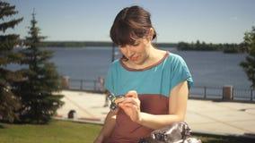Uma jovem mulher torce nas mãos de um girador do brinquedo que senta-se na margem filme